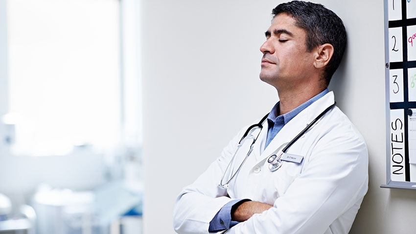 internist closing eyes and leaning against wall