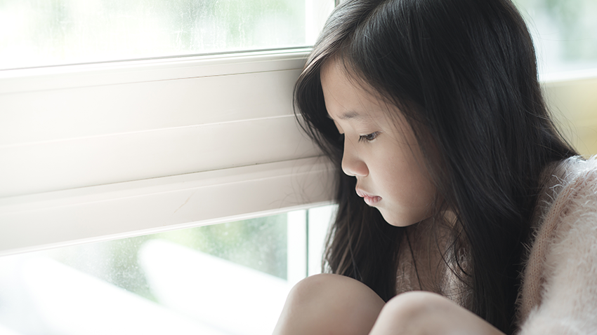 Sad young girl looking out a window