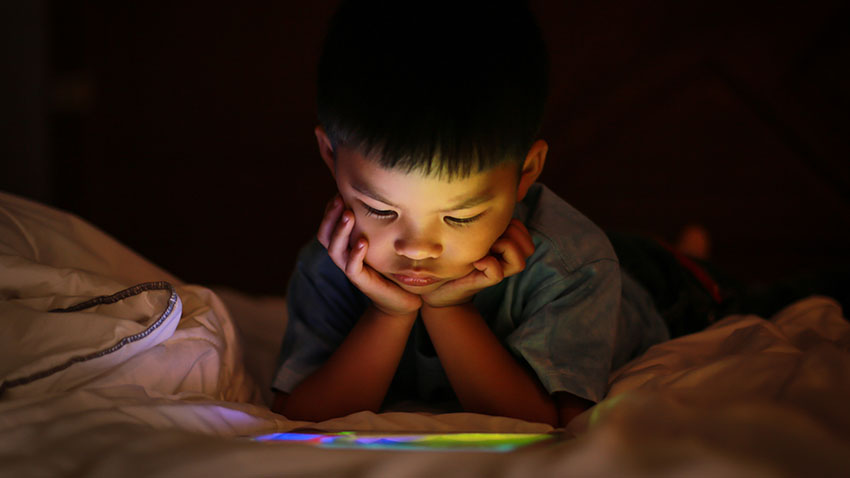 Child with ipad in bed
