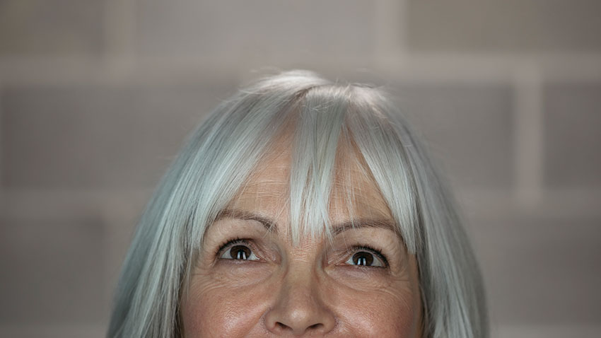 Woman with white hair looking up
