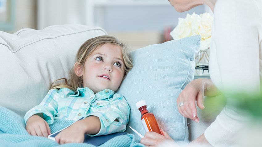 Little girl in bed with a woman next to her with a bottle of medicine in her hand