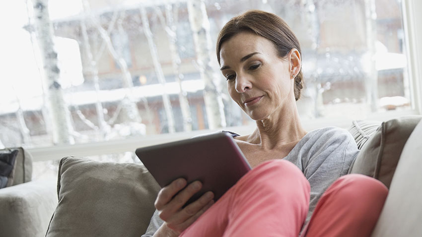 Woman sitting on a sofa reading from an ipad