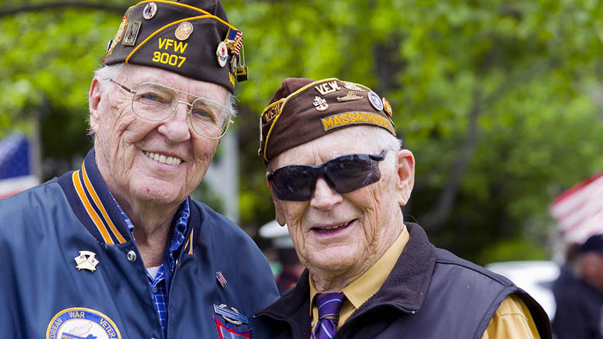 Two veterans smiling at camera outside.