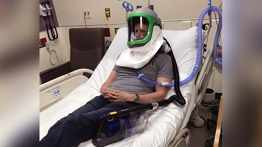 Man laying in hospital bed showing how portable negative pressure helmet would look
