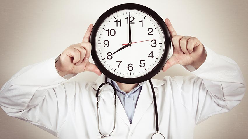 physician holding clock for head