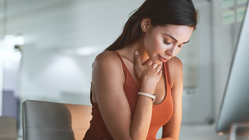 female wearing orange tank top holding her throat in discomfort and looking down