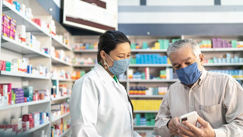 doctor helping gentleman looking at pills in pharmacy