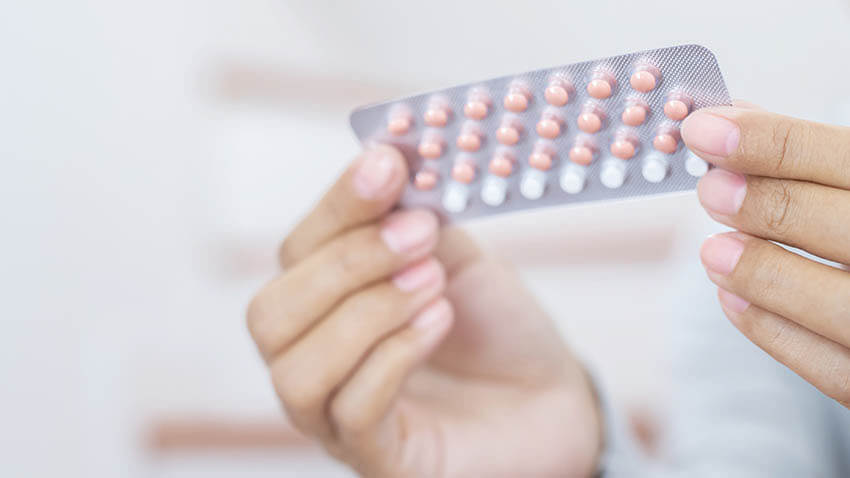 Woman hands opening birth control pills