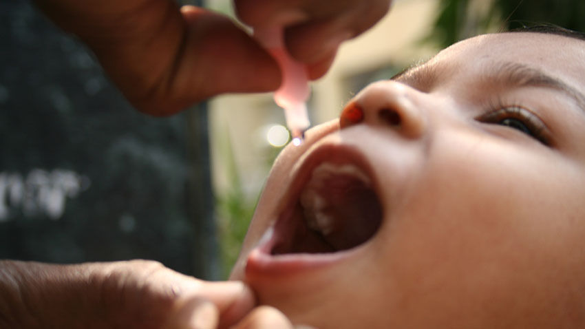 child receiving polio vaccine drops