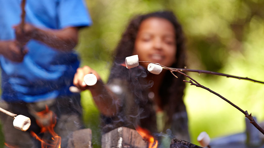 child holding stick of marshmallows over camp fire