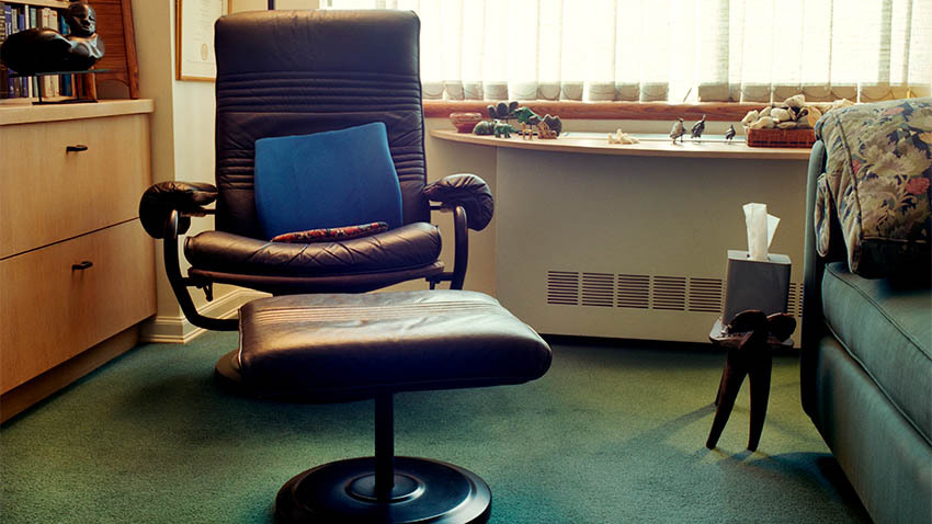 maroon office chair with blue pillow in it with foot rest and green couch next to it with green carpet on floor