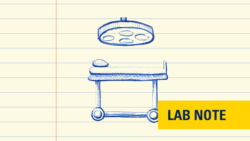 "drawing in blue ink of surgery table and light overhead with lower left corner yellow badge with dark blue font writing saying ""lab note"""