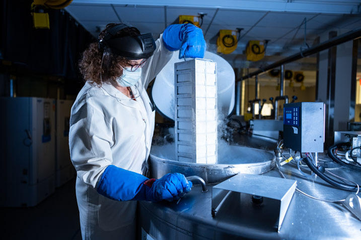 person lifting samples in biorepository with blue gloves, white coat and mask and goggles on