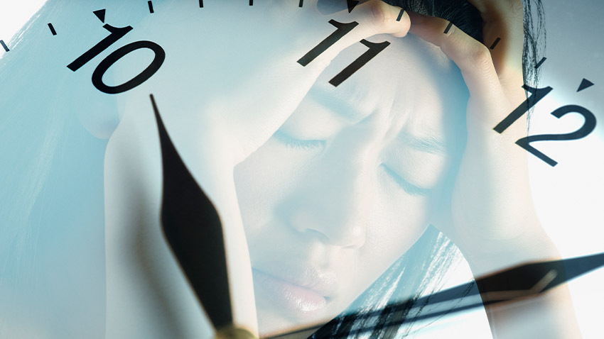 woman reflected in clock holding head in pain