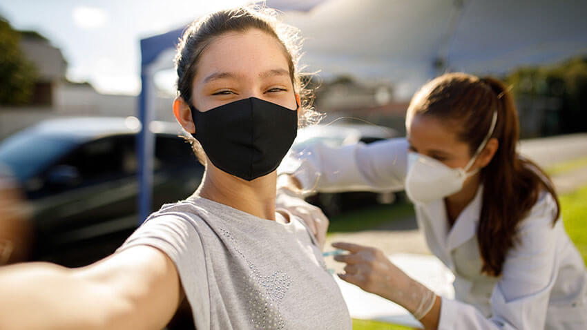 Teen taking a selfie with vaccination doctor mask on.