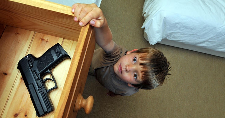 Child reaching for a gun laying in an open drawer