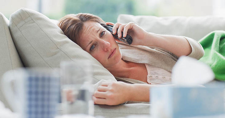 woman sick on couch on phone