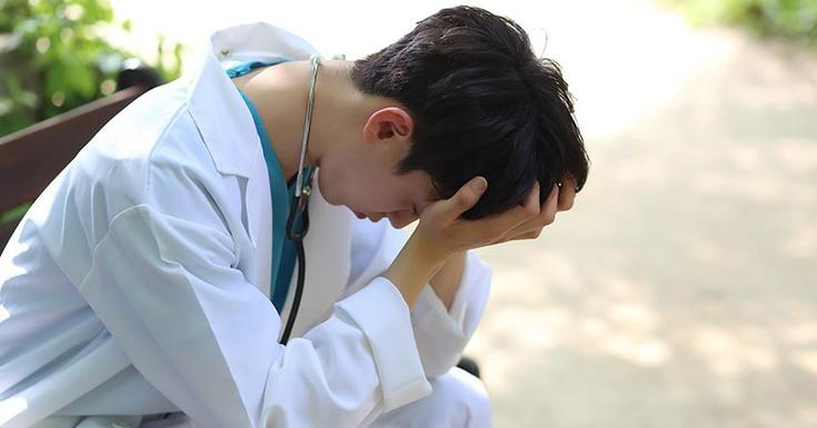 young doctor stressed on park bench