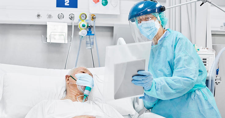 older patient in white hospital gown in ICU with doctor in blue protective gown and equipment and face shield holding ipad up