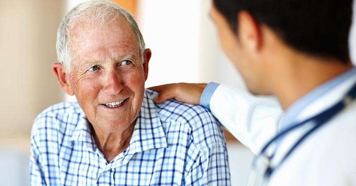 older gentleman in blue checkered shirt talking with doctor