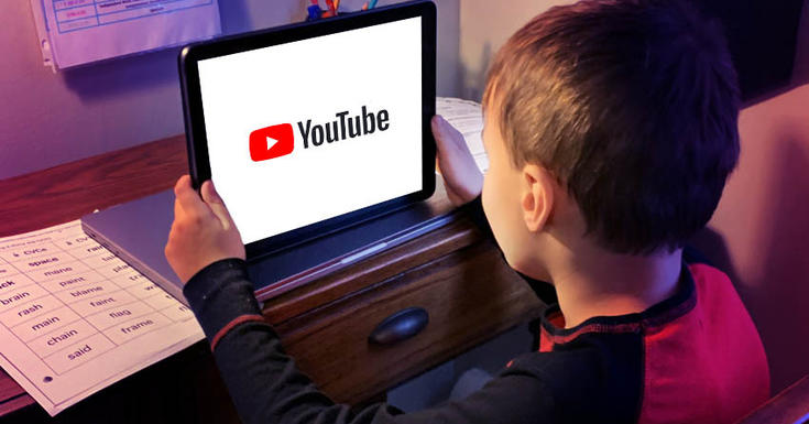 kid sitting watching youtube on tablet screen