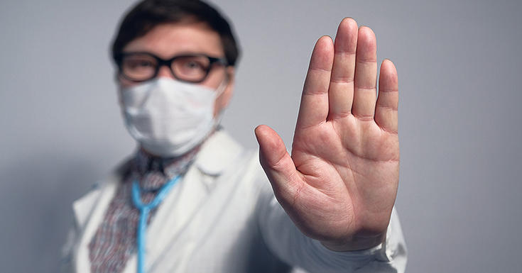 doctor holding hand up in mask with glasses and mask