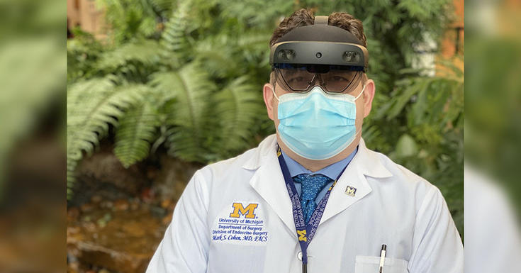 doctor outside in white coat with headset on and blue mask on in front of greenery