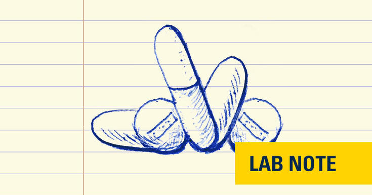 lined paper with blue ink drawing of pills with yellow badge with blue font on bottom right saying lab note