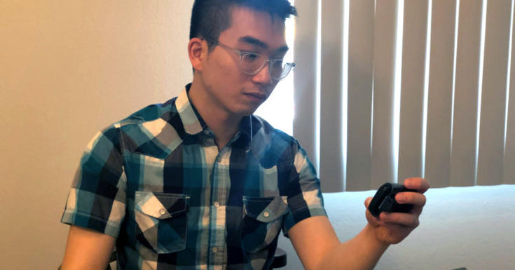 Young man in plaid shirt looking at pager