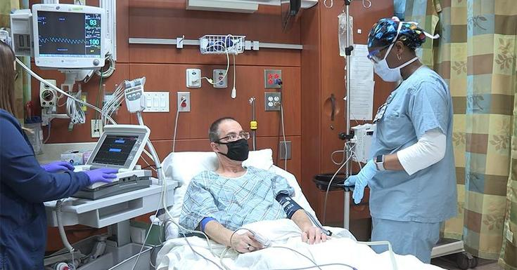 patient in bed with mask on and clinician visiting at bedside with mask on