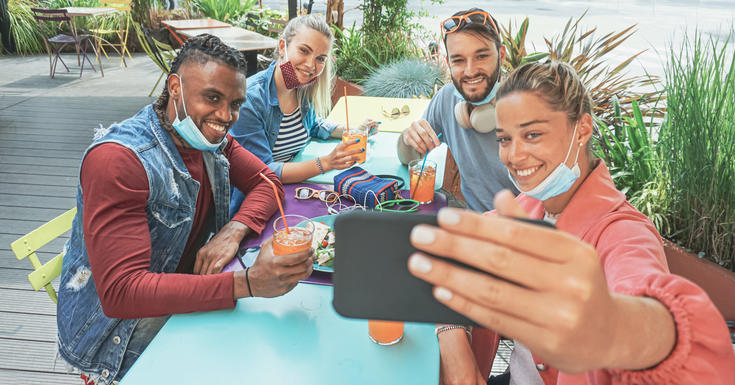 people sitting together with masks pulled down taking a selfie at a picnic table