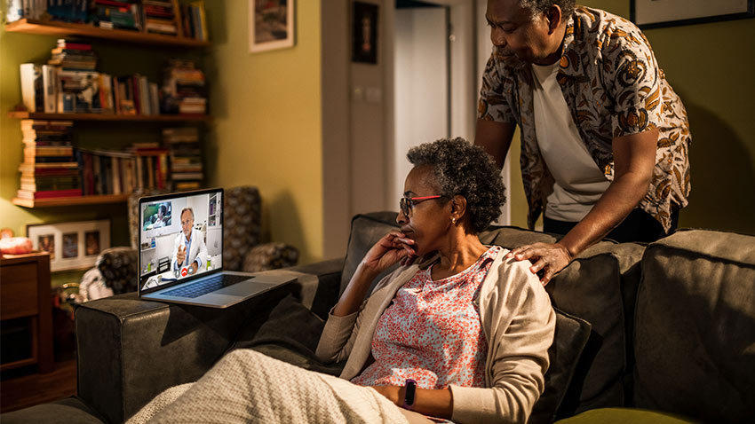 senior couple on couch with doctor on laptop