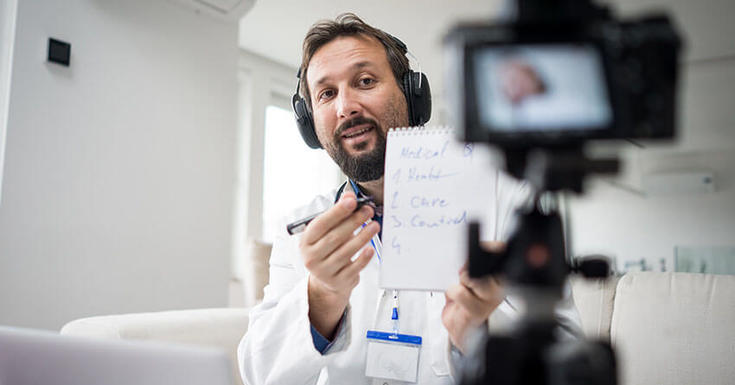 Doctor talking into camera in clinic holding notepad