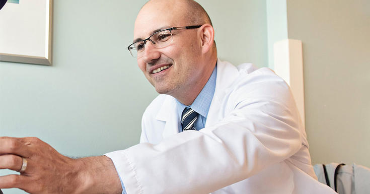 Doctor in room reaching out smiling
