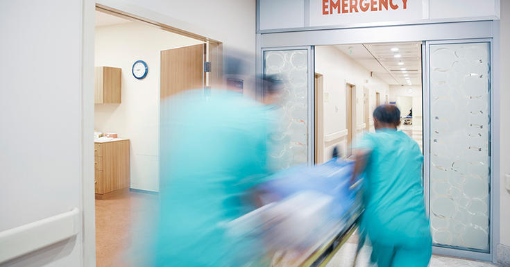 3 doctors rushing blurry into emergency room hospital in teal scrubs with stretcher