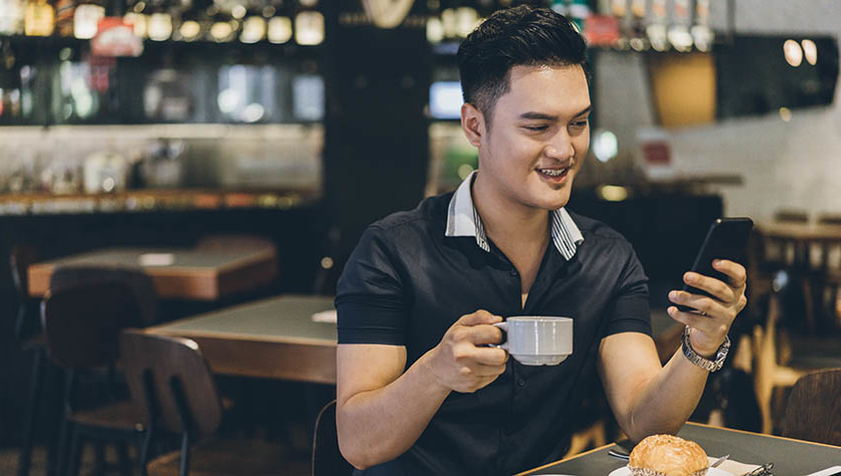 Man drinking coffee and looking at cell phone